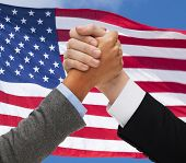 partnership, politics, gesture and people concept - close up of two hands armwrestling over american flag