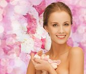 beauty, people and health concept - beautiful smiling young woman with flowers and bare shoulders over pink floral background
