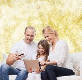 family, holidays, shopping, technology and people - smiling family with tablet pc computer and credit card over yellow lights background