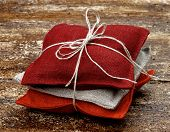 foto of sachets  - Stack of Textile Sachet Pillows with Sack Rope and Bow on Textured Wooden background - JPG