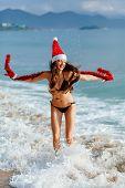 Santa Girl Jumping In The Sea On The Beach