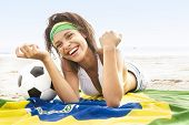 Attractive mixed race girl with Brazil flag on beach