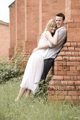 Young beautiful couple outdoors against brick building