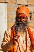 JAISALMER, INDIA - NOVEMBER 28, 2012: Indian sadhu (holy man) blessing. Sadhus are holy men who live ascetic life and focus on spiritual practice of Hinduism