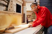 stock photo of carpentry  - Apprentice Using Circular Saw In Carpentry Workshop - JPG