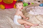 image of baby diapers  - Cute blonde baby girl with beautiful blue eyes sits on bed in diapers with toy - JPG