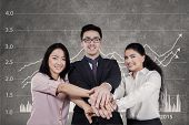 foto of joining hands  - Three multiracial businesspeople smiling at the camera while joining their hands with financial graph background - JPG