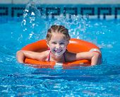 foto of lifeline  - happy cute  girl swims with a lifeline in the pool in  summer - JPG