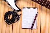 pic of sounding-rod  - electric guitar and memo pad on wooden table - JPG