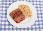 picture of meatloaf  - Slices of fresh homemade meatloaf on a white plate with brown rice on blue check placemat - JPG