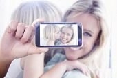 stock photo of hand kiss  - Hand holding smartphone showing against mother sitting on the couch with her daughter kissing her cheek - JPG