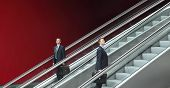 image of escalator  - business man going up and down escalators concept of choice and success - JPG