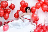 foto of laying-in-bed  - Young pregnant woman laying on a bed and holding a tummy red balloons around - JPG