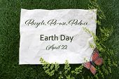 stock photo of reuse recycle  - Earth Day April 22 Concept with recycled paper in grass with fern and butterfly and text - JPG
