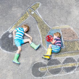 foto of excavator  - Two little happy kid boys having fun with excavator picture drawing with colorful chalk - JPG