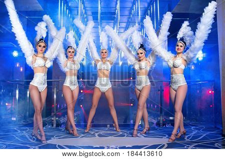 poster of Full length shot of five gorgeous women dancing wearing white carnival outfits nightclub festival festive disco dance performance showgirls show time entertainment leisure enjoyment happiness.