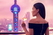 Elegant asian woman in gown drinking white wine glass at rooftop bar terrace looking at city lights  poster