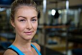 Portrait of smiling fit woman in fitness studio poster