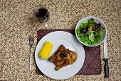 Plate of roast chicken with corn, salad and red wine