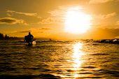 Pôr do sol sobre o oceano com surfistas