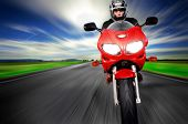 Motorcycle moving very fast along motion blurred road