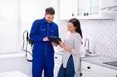 Young Male Pest Control Worker Showing Invoice To Woman In Domestic Kitchen poster