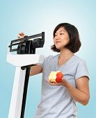 Woman Weighing Herself On Scale With Apple