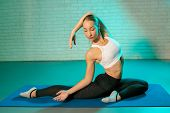Handsome Young Slim Gymnast Woman In Sports Clothing Stretching On Brick Wall In Neon Lights. Flexib poster