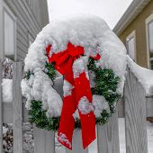 Snow Covered Wreath On White Picket Fence In Utah poster