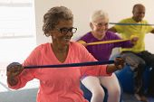 Happy senior woman exercising with resistance band in fitness studio poster