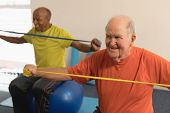 Front view of senior man exercising with resistance band in fitness studio poster
