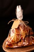 Fresh Homemade French Croissants With Filling In A Transparent Cellophane Bag With A Tag On A Black poster
