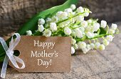 Bouquet Of Lilies Of The Valley With Happy Mothers Day Tag Card On Wooden Background.lily-of-the-val poster