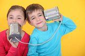 Llaman a los niños tener un teléfono con latas sobre fondo amarillo