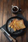 French Toasts With Fried Plantains, Dripping Maple Syrup, Sugar Powder On A Black Plate. French Dess poster