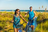 Summer people lifestyle happy couple biking on beach relaxing outdoors activity at sunset. Young wom poster