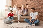 Happy Family Playing Video Games In Living Room poster