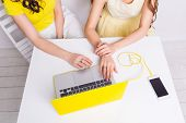 Close-up Of A Table With A Laptop In Yellow Case And Smartphone On Yellow Charger. Two Girls Sit Beh poster