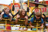 Teenagers Enjoy An Exciting Carnival Ride