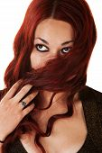 pic of fidget  - Young woman covering her mouth with long red hair - JPG