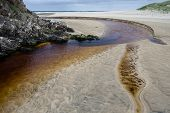 Iron Coloured Stream Flowing Into The Sea.