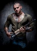 Muscular Tattooed Man With Jackhammer Posing Over Grey Background