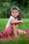 Portrait Of Little Bully Girl Sitting On Plaid In Grass