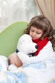Little Sick Girl With Scarf Embraces Toy Bear In Bed