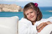 Little Girl In White Bathrobe Relaxing On Terrace Sea Background