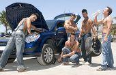 Men Changing A Wheel Under The Sun