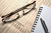 Glasses, Pen And Notebook Laying On Newspaper With Financial Numeric Data.