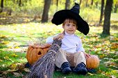 Little Boy With Two Halloween Pumpkins, A Broom And A Hat In A Forest