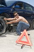 Man Changing A Broken Wheel Of His Car