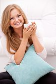 Young, happy woman smiling and holding white cup at home